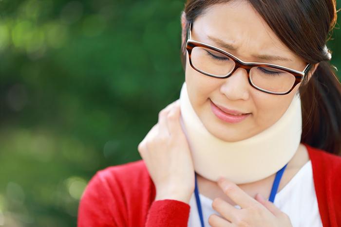 首サポーターをつけた悩み顔の女性