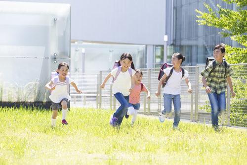 芝生の上を駆け回る子ども達