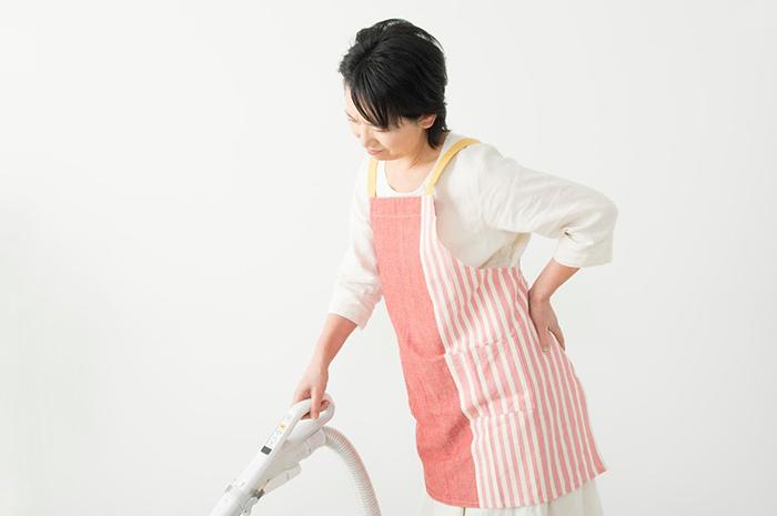 掃除機をかけながら腰をさする女性
